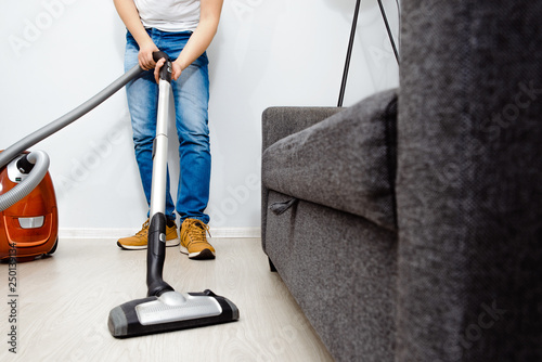 The man is vacuuming in the apartment Fototapet
