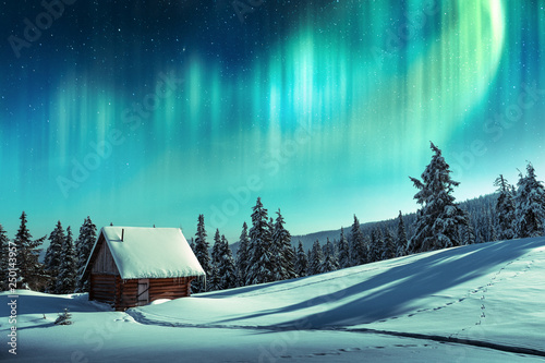 Aurore polaire Fantastic winter landscape with wooden house in snowy mountains and northen light in night sky