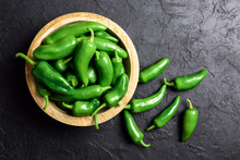 Green Jalapeno Hot Pepper In Wooden Plate Closeup. Food Photography