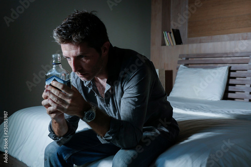 young depressed and wasted drunk man drinking vodka bottle at home sitting on be Canvas Print