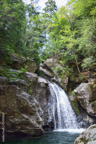 Waterfall rushing over rocks in lush green forest New England landscape