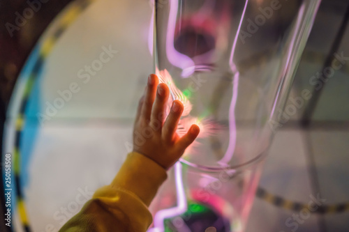 Foto  Hand of a boytauching the tube with glowing gas