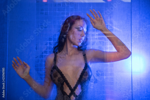 Seductive sexy woman in the shower leaning on glass with steam wearing sexy lingerie