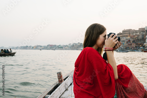 Photo Traveler on a boat taking photos from the River Ganges