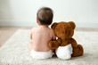 canvas print picture - Back of a baby with a teddy bear