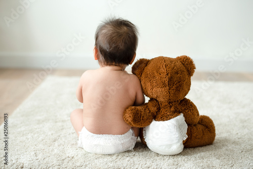 Fotografiet  Back of a baby with a teddy bear