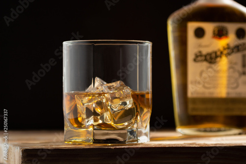 Photo Glass of whiskey with ice cubes on a wooden table and dark background