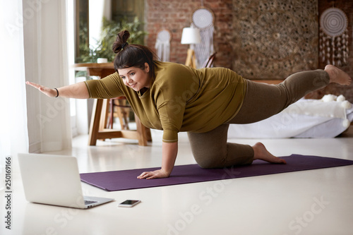 Fotografie, Obraz  Obese chubby young European female with hair knot practicing yoga or pilates ind