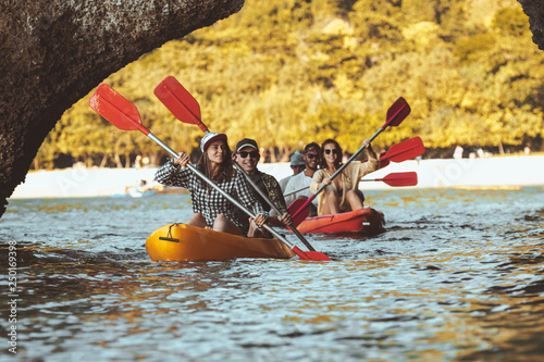 Valokuva  Group of happy friends walks by kayaks under big rocks in the sea