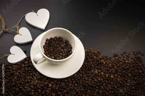 Filiżanka kawy pełne ziarna kawy z trzema białymi sercami