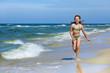 Little girl in swimsuit running on the beach