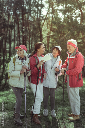 Group of tourists using a tablet while hiking Fototapeta