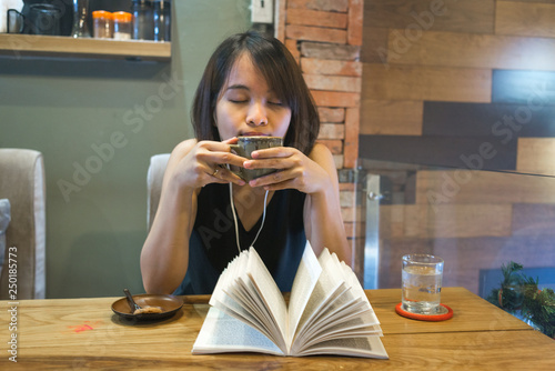 Fotografie, Obraz  Asian woman enjoy free time with book, coffee and music