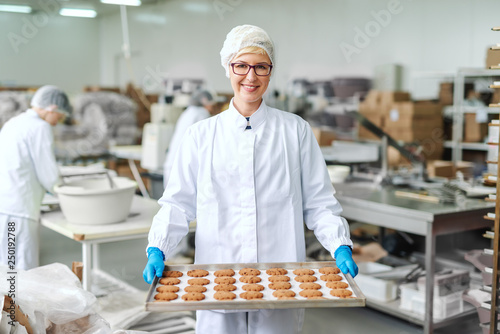 Pinturas sobre lienzo  Smiling blonde Caucasian employee in sterile uniform and with eyeglasses standing and holding tray with cookies