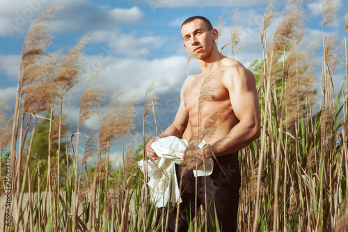 Fotografie, Obraz  Young macho man with a beautiful sports figure standing in the grass and holding his shirt
