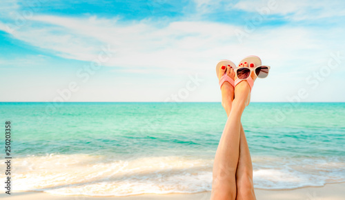Poster Pedicure Upside woman feet and red pedicure wear pink sandals, sunglasses at seaside. Funny and happy fashion young woman relax on vacation. Girl on beach. Creative for tour agent. Weekend travel. Summer vibes