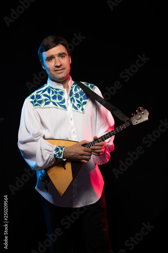 Fotografia  A brunette man in a folk shirt plays a balalaika in scenic blue and red light on
