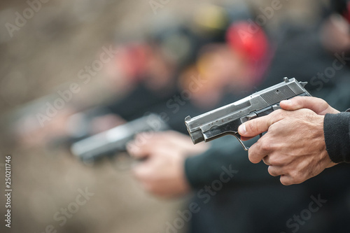 Fotomural  Close-up view of shooter practice handgun shooting in row group