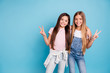 canvas print picture - Portrait of two people nice cute lovable lovely sweet charming dreamy attractive cheerful straight-haired pre-teen girls siblings showing v-sign isolated on blue turquoise background