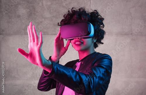 Cute black teenager exploring virtual reality near concrete wall Wallpaper Mural