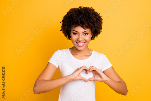 Close up photo beautiful amazing she her dark skin lady hands arms sweetheart figure healthy heart safety message wear casual white t-shirt isolated yellow bright vibrant background