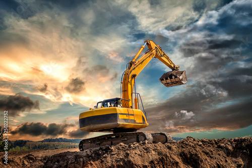 Fototapeta Crawler excavator during earthmoving works on construction site at sunset