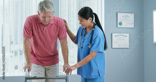 Obraz na plátně Physical therapist or doctor helping older male patient learn to walk with a walker