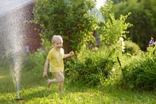 Funny Little Boy Playing With Garden Sprinkler In Sunny Backyard