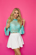 canvas print picture - Beautiful Woman In Turquoise Lace Blouse And White Mini Skirt On Pink Background