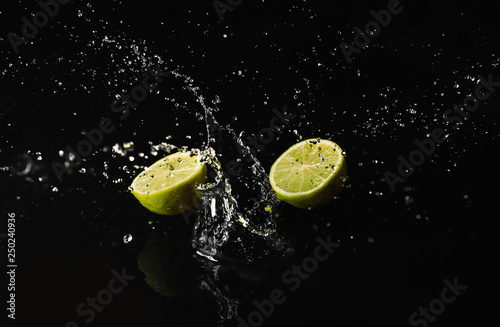Ripe cut lime with water splash on dark background