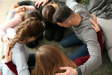 Group Of People Praying Together Indoors
