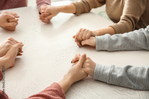 Group of people praying together at table Canvas Print