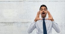 Business, Stress And People Concept - Indian Businessman Shouting Or Calling Over Gray Concrete Wall Background