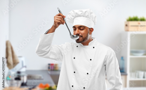 Photo cooking, profession and people concept - happy male indian chef in toque tasting