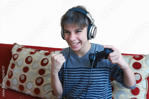 Foto  teenage boy with headphones on his head emotionally of plays in a game console w