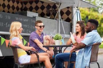 leisure and people concept - happy friends with drinks sitting at table at food truck
