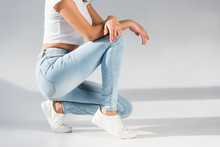 Cropped View Of Stylish Woman In Jeans Sitting On Grey Background
