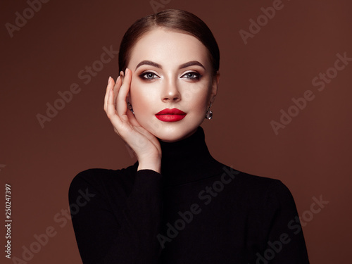 Fotobehang womenART Beautiful Young Woman with Clean Fresh Skin. Perfect Makeup. Beauty Fashion. Red Lips. Cosmetic Eyeshadow. Smooth Hair. Girl in Black Turtleneck