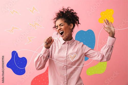 Fotografie, Obraz Beautiful young african woman posing isolated over pink wall background screaming singing
