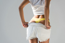 Cropped View Of Woman In Yellow Panties Taking Off Shorts On Grey Background