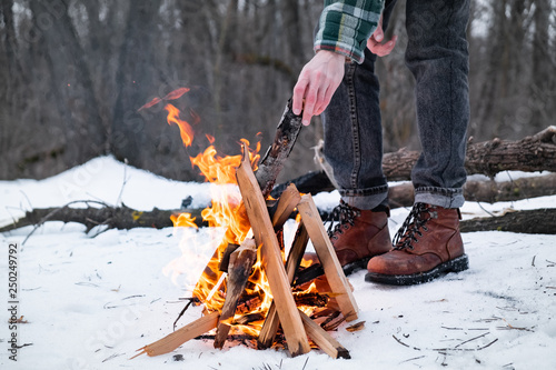 Fotografie, Obraz  Making a campfire in a snowy forest