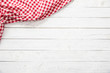 canvas print picture - Red checkered kitchen tablecloth on wooden table.