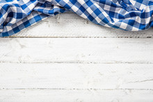 Blue Checkered Kitchen Tablecloth On Wooden Table.