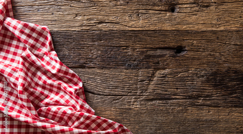 Red checkered kitchen tablecloth on rustic wooden table Fototapeta