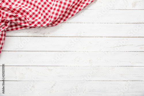 Fotografie, Obraz  Red checkered kitchen tablecloth on wooden table.