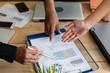 In selective focus human hand with pen pointing at business paper chart,meeting for discuss deal,at office,blurry light around