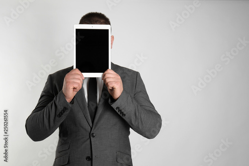 Fotografía  Businessman hiding face behind tablet computer on light background