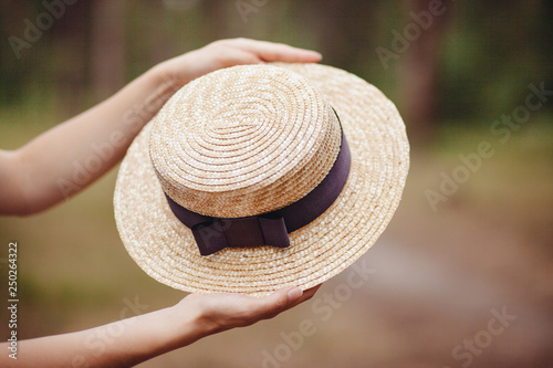 Photo Hands with boater straw hat outdoors, french style fashion