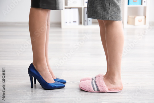 Fotografía  Women in slippers and high heeled shoes in office