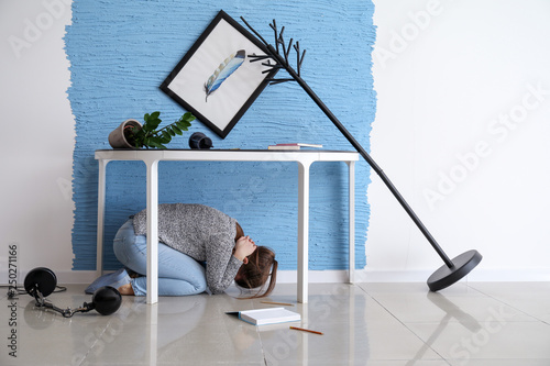 Canvas Print Young woman hiding under table during earthquake
